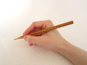 ノートに鉛筆で書き込む手