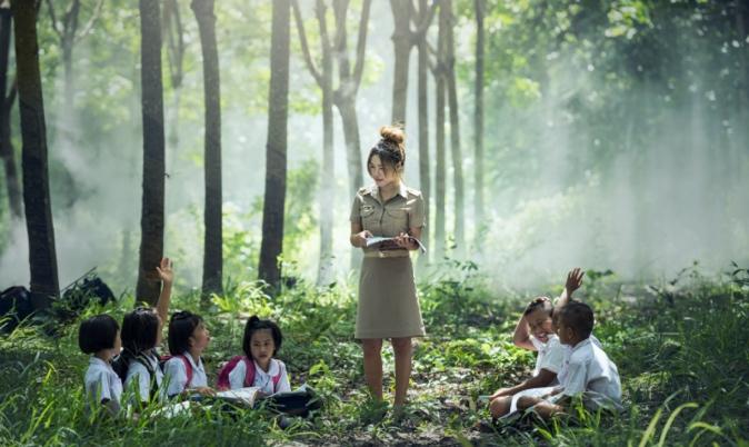 森の中で授業をしている先生と生徒