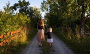 田舎道で手を繋いで歩く親子