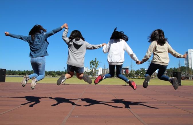 手をつないでジャンプする女の子たち