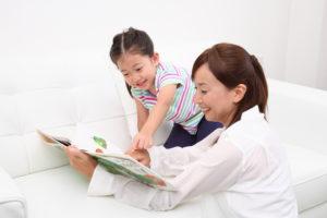絵本をみる女の子とお母さん