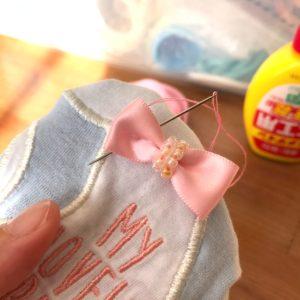服にリボンを縫い付ける